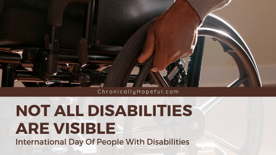 Man in a wheelchair with his hand on the wheel. Title reads: Not all disabilities are visible. International day of people with disabilities.