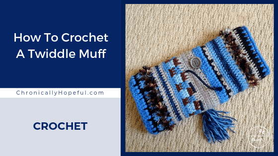 A crocheted twiddle muff with tassels and buttons on it lying on the carpet. Title reads, How to crochet s twiddle muff