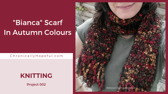 Char wearing a knitted scarf she made. It's black with autumn colour speckles. TItle reads: Knitting project 2, Bianca scarf in autumn colours