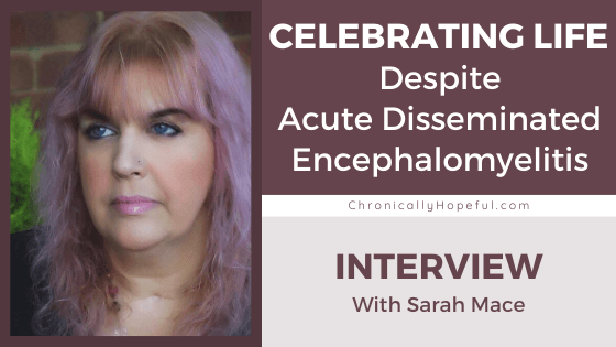 Sarah standing in front of a brick wall. She has pink hair and a black top. Title reads: Celebrating life despite Acute Dissemminated Encephalomyelitis. Interview with Sarah.